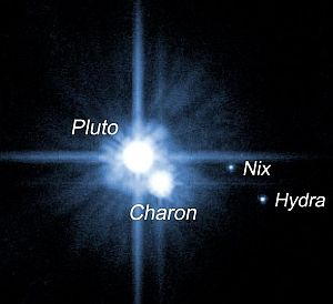 The dwarf planet Pluto, showing three of its five moons